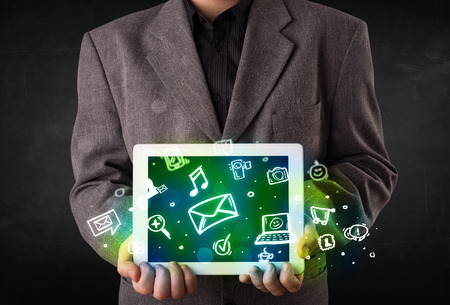 Person holding a white tablet with media icons and symbols photo