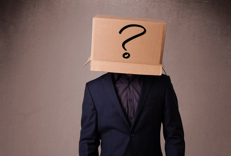 boxy: Young man standing and gesturing with a cardboard box on his head with question mark Stock Photo