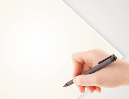 person writing: A person writing on a plain white blank paper with a balpoint pen Stock Photo