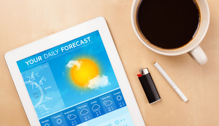 Workplace with tablet pc showing weather forecast and a cup of coffee on a wooden work table close-up photo