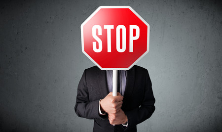 Businessman standing and holding a stop sign in front of his head Stock Photo