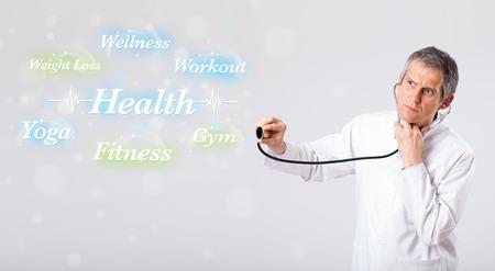 signos vitales: Ancianos médico clínico que apunta a la colección de la salud y de la aptitud de las palabras