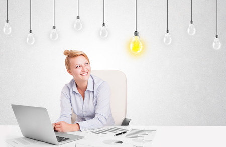 Business woman sitting at table with bright idea light bulbs