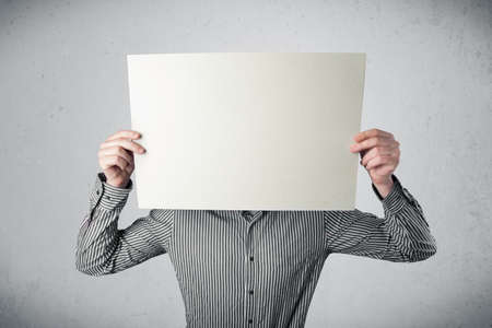 hidden success: Businessman standing and holding in front of his head a white paper with copy space Stock Photo