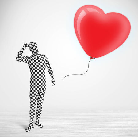 Cute guy in morpsuit body suit looking at a red balloon shaped heart photo