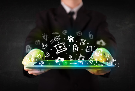 Person holding tablet pc with green media icons and symbols photo