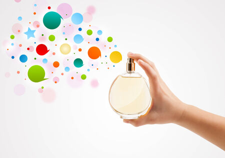 close up of woman hands spraying colorful bubbles from beautiful perfume bottle photo
