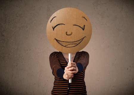 happy young: Young lady holding a cardboard smiley face emoticon in front of her head Stock Photo
