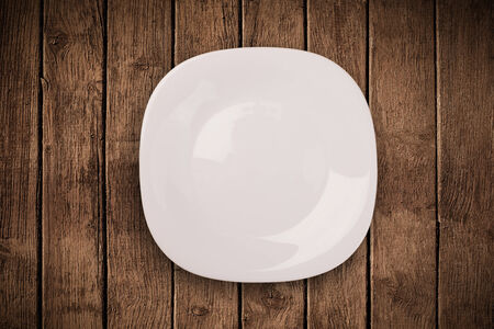 Colorful empty shiny plate on grungy background table  photo