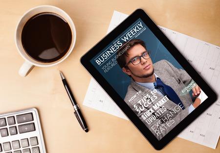 Lugar de trabajo con PC de la tableta portada de la revista muestra y una taza de café en una mesa de trabajo de madera de cerca