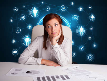 Young businesswoman sitting at desk with social network icons photo