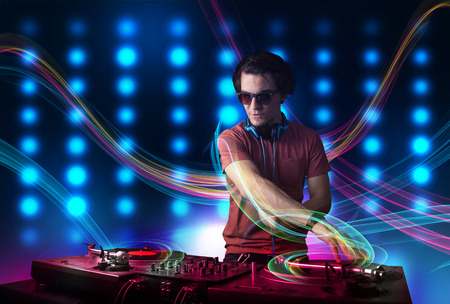 Attractive young Dj mixing records with colorful lights photo