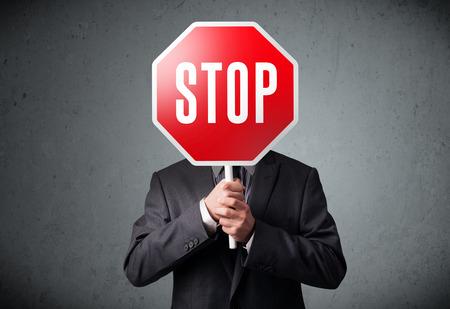 warning: Empresario de pie y sosteniendo una se�al de stop en el frente de su cabeza Foto de archivo