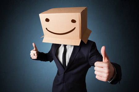 man thinking: Businessman standing and gesturing with a cardboard box on his head with smiley face Stock Photo