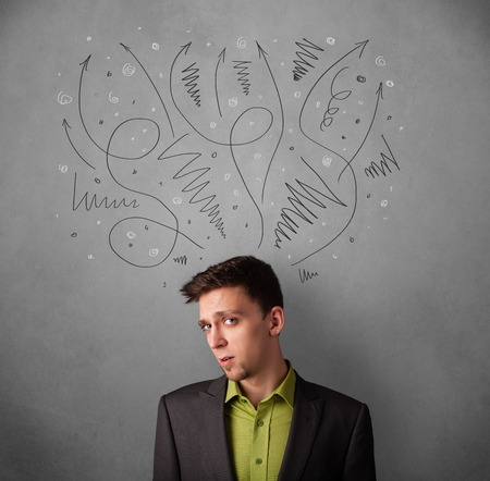Young businessman deciding with sketched arrows over his head photo