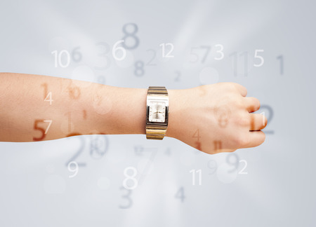 Hand with watch and numbers comming out on the side photo
