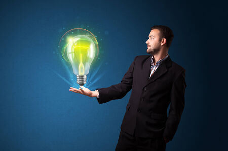 Young businessman holding glowing lightbulb in his hand photo
