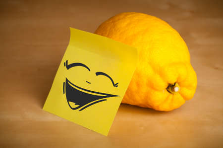 Drawn smiley face on a post-it note sticked on a lemon photo