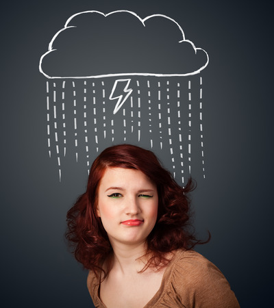 Thoughtful young woman with thundercloud above her head photo
