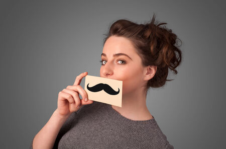Happy cute girl holding paper with mustache drawing on gradient background photo