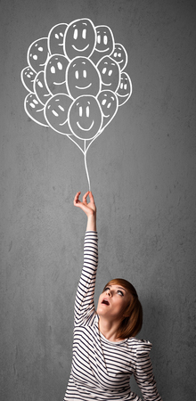 Young woman holding a bunch of smiling balloons photo