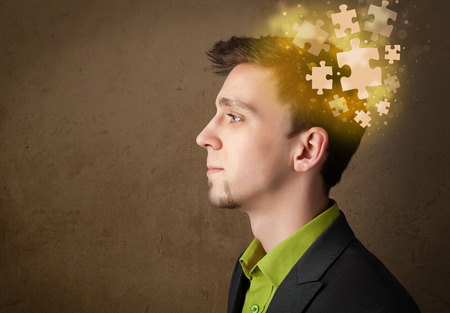 Young person thinking with glowing puzzle mind on grungy background photo