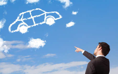 Handsome young man looking at car cloud on a blue sky photo