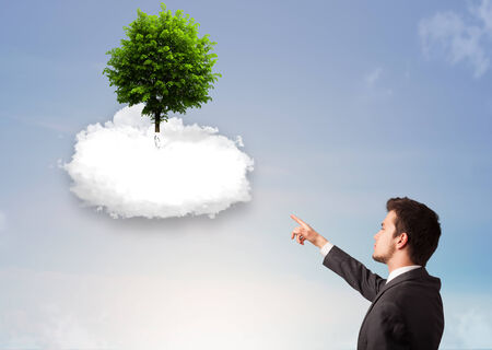 Young man pointing at a green tree on top of a white cloud concept photo