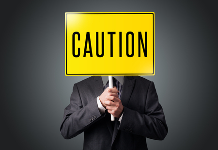 Businessman standing and holding a yellow caution sign in front of his head photo