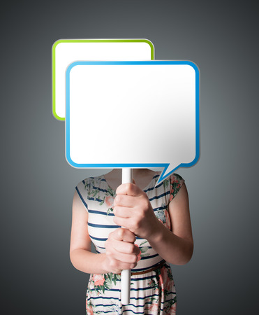 Young lady standing and holding an empty speech bubble in front of her head photo