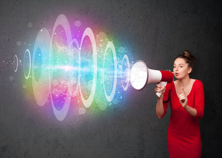 Cute young girl yells into a loudspeaker and colorful energy beam comes out photo