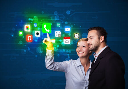 Business couple pressing colorful mobile app icons with bokeh background  photo