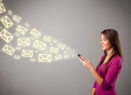 attractive young lady standing and holding a phone with message icons photo