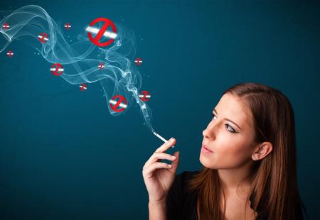 Beautiful young woman smoking dangerous cigarette with no smoking signs photo