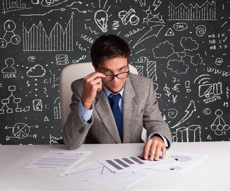 Young businessman sitting at desk with business scheme and icons photo