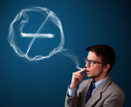 unhealthy: Handsome young man smoking unhealthy cigarette with no smoking sign Stock Photo