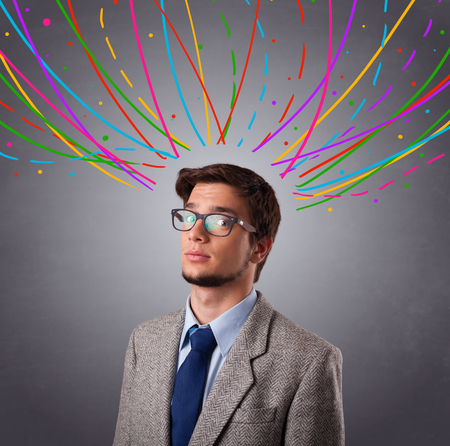 Young man standing and thinking wiht colorful abstract lines overhead photo
