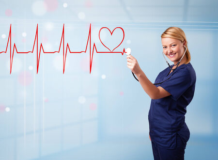 Beautiful young nurse listening to abstract pulse with red heart photo