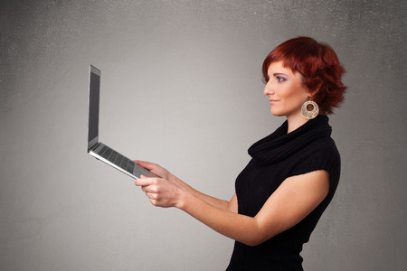 Pretty young woman holding modern laptot photo