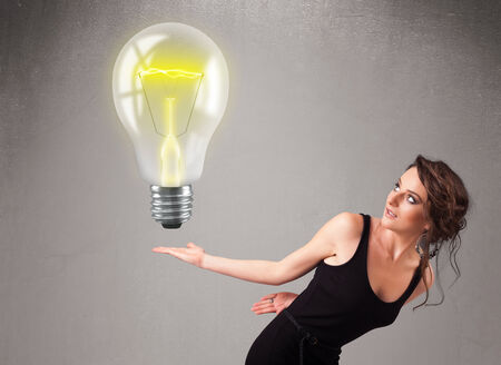 Beautiful young lady holding realistic 3d light bulb photo