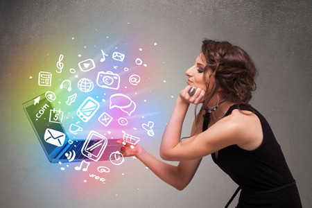Beautiful young woman holding notebook with colorful hand drawn multimedia icons photo