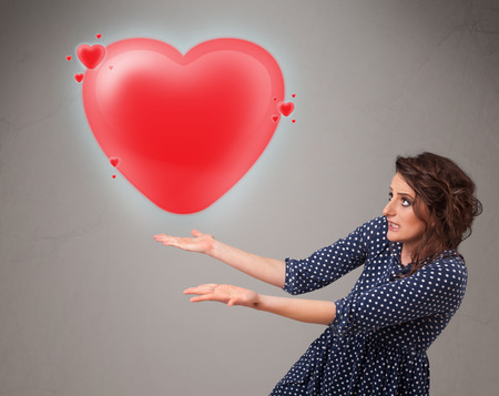 Beautiful young lady holding lovely 3d red heart photo
