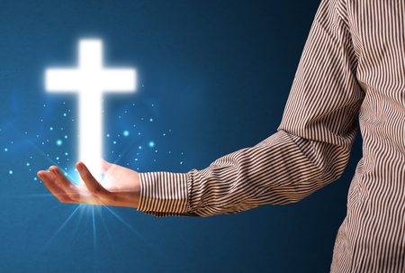 jesus standing: Young businessman holding a glowing cross in his hand