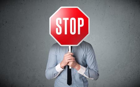 Empresario de pie y sosteniendo una señal de stop en el frente de su cabeza Foto de archivo - 29287439