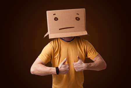 masquerader: Young man standing and gesturing with a cardboard box on his head with straight face Stock Photo