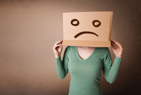 hiding face: Young girl standing and gesturing with brown cardboard box on her head with sad face Stock Photo