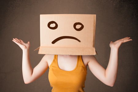 woeful: Young girl standing and gesturing with brown cardboard box on her head with sad face Stock Photo