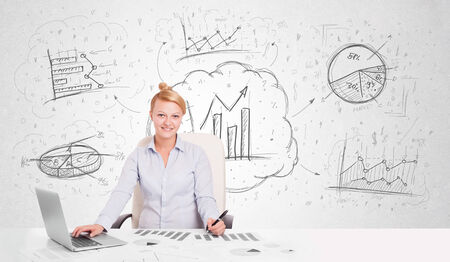Business woman sitting at white table with hand drawn graph charts photo