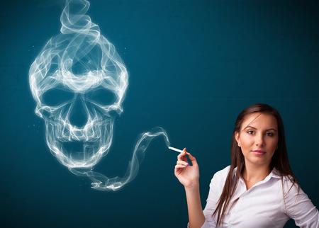 Pretty young woman smoking dangerous cigarette with toxic skull smoke  photo