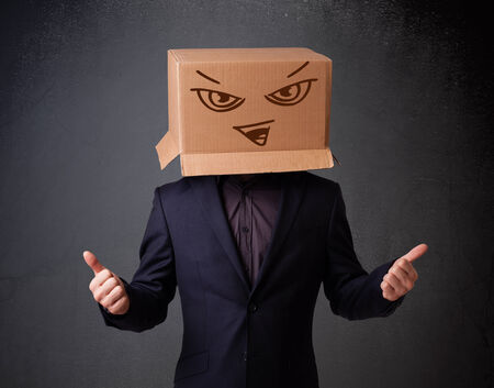 boxy: Young man standing and gesturing with a cardboard box on his head with evil face